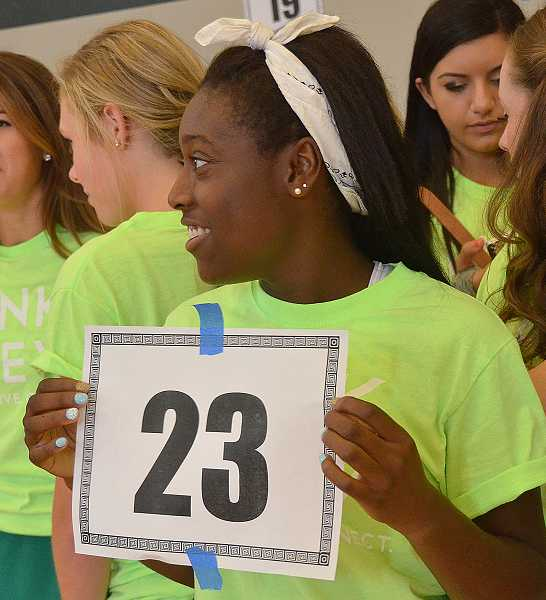 by: TIDINGS PHOTO: VERN UYETAKE - Kayley Arzu holds her sign directing the freshmen in her group where to meet during their first day Sept. 3.