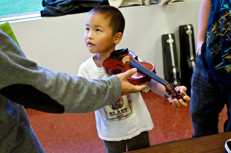 by: TIMES PHOTO: JAIME VALDEZ - Jaiden, a first-grader at Bethany Elementary School, listens to instructions by Jake Schmidt of Beaverton Music Services on how to play the violin.