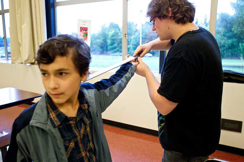 by: TIMES PHOTO: JAIME VALDEZ - Carlos Ferrer, a seventh-grader at the Arts and Communication Magnet Academy, stands with his arm extended while being sized for a viola by Jake Schmidt of Beaverton Music Services.