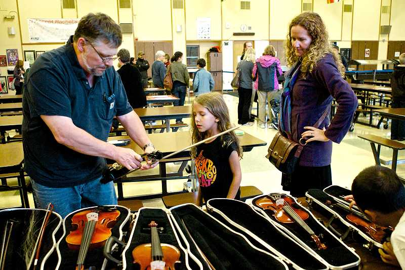 by: TIMES PHOTO: JAIME VALDEZ - Jake Schmidt of Beaverton Music Services shows Aurora McCrary-Bond, a second-grader at Ridgewood Elementary School and her mother, Kelola, the type of violin she will be playing at South West Music School.