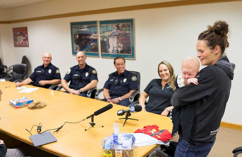by: TIMES PHOTO: CHASE ALLGOOD - Katlyn Marquess holds 1-month-old Thor Hoffman as she chats with the 911 operator and paramedics who helped her through his delivery.