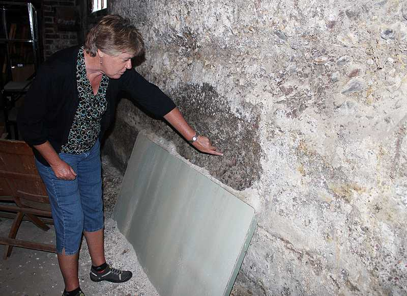 by: HOLLY M. GILL - Kathie Rohde, county finance director, shows the deterioration of the basement walls.