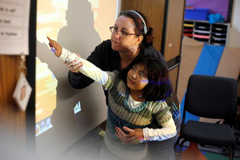 by: TIMES PHOTO: JONATHAN HOUSE - McKinley Elementary School special education teacher Susan Bomber helps Ariana Marquez with a word association exercise using the class smart board, an interactive whiteboard that can be touched. Through Donors Choose and the Fuel Your School drive, Bomber's class has received funds to purchase new classroom eqiupment that she may have otherwise had to purchase herself.