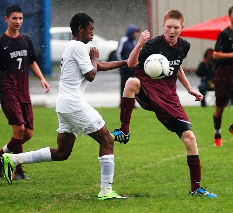 by: DAN BROOD - IN THE RAIN -- Sherwood sophomore Logan Jones (right) keeps the ball away from Glencoe's Jeremiah Burton during Tuesday's match at Hare Field. The Crimson Tide got a 1-0 victory.