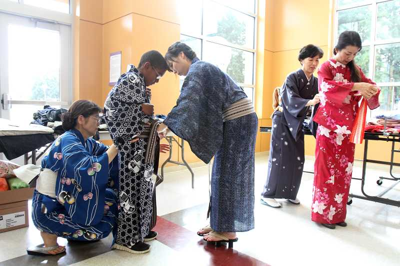 by: TIMES PHOTO: JONATHAN HOUSE - Beaverton Internation School student Isaac Vergun is helped with putting on a kimono by Shoko Nagasaki, left, and Izumi Nakada during a workshop this week.
