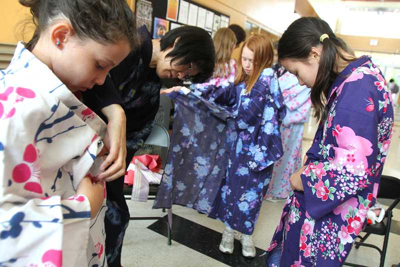 by: TIMES PHOTO: JONATHAN HOUSE - Hiroko Kawabata helps Ella Alves de Lima with her kimono, while fellow International School of Beaverton students Meredith McMahon, center, and Anna Bakun figure out how to put their's on.