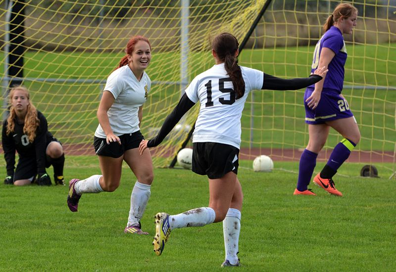 by: JOHN WILLIAM HOWARD - St. Helens forward Ashley Giesbers (left) celebrates after scoring the opening goal against Hermiston. Geisbers scored a pair in the match, the second coming on a penalty kick in the second half.