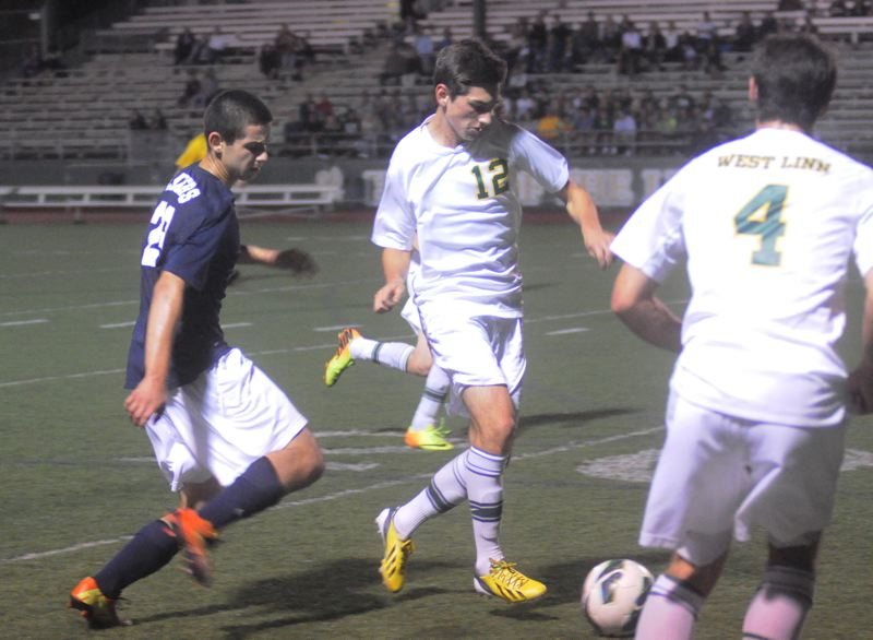 by: MATT SHERMAN - West Linn's Kegan Wesley looks to make a pass on an attack for the Lions during the team's 1-0 win over Lake Oswego last week. The Lions scored in the final minute of the first half to seal the victory.