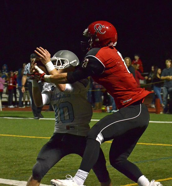 by: VERN UYETAKE - Lakeridge's Tyler Miller fights for a pass against an Oregon City receiver in last week's league opener for both teams at Pioneer Stadium.