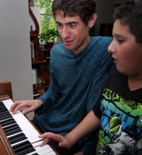 by: OUTLOOK PHOTO: JIM CLARK - Everett Davis uses music to help children with learning disabilities find a sense of pride and accomplishment in a skill. Nine-year old Ryan Woodward is learning the fundamentals of the piano.