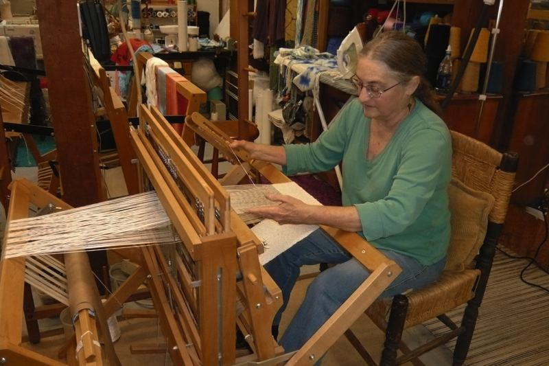 by: BOOM PHOTO: JANIE L. NAFSINGER - Sylvia Emard weaves a swath of rayon fabric that she will fashion into two scarves.