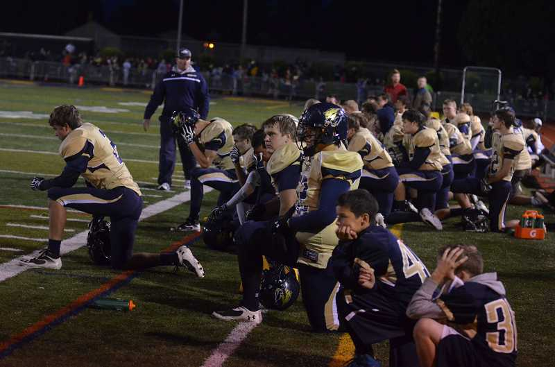 by: JEFF GOODMAN - Members of the Canby football team kneel along the sideline Sept. 27 at Cougar Stadium as medical personnel tend to senior Sam Bodine. The linebacker suffered a season-ending leg injury in Canby's 20-15 win over Oregon City.