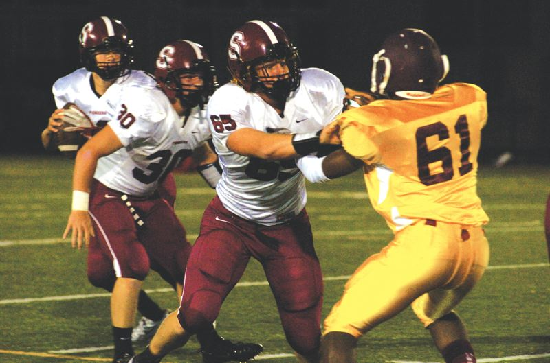 by: SANDY POST: DAVID BALL - Sandy tackle Andrew Spencer lays down a block, while QB Spencer Barnett looks for an open receiver during Fridays 21-0 road win over Milwaukie.