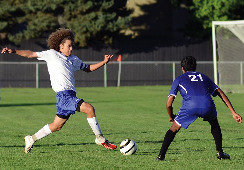 by: HILLSBORO TRIBUNE PHOTO: CHASE ALLGOOD - Hillsboro senior forward Tyler Hoiem dribbles the ball upfield against pressure from Woodburn defender Christian Andrade during last Thursday's non-conference soccer match, which the Spartans won 2-0.