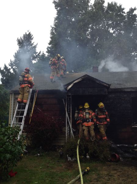 by: CFD NO. 1 - Personnel from Clackamas Fire work to extiguish a suspected arson on a drug-filled house in Clackamas on Friday afternoon.