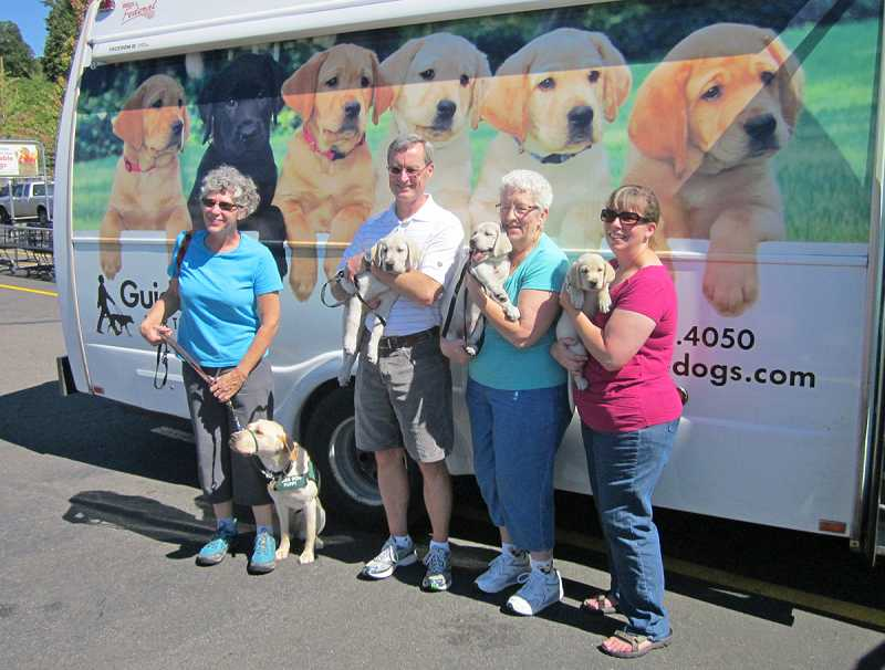 by: BARBARA SHERMAN - NEW ARRIVALS - Posing for a photo after the Guide Dogs for the Blind special delivery of new pups Aug. 17 are Sandy (left) with her year-old guide dog puppy, Olive, next to the three new puppy-raisers, Steve with Gracious, Lou Travis with Gobi and Barb with Iris.