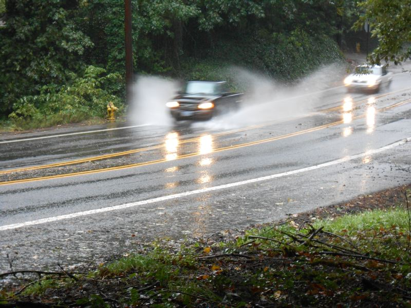 by: WEST LINN TIDING: J. BRIAN MONIHAN - Vehicles splash through a large puddle on Highway 43 in West Linn Monday after this weekend's big storm blew through and dumped a record amount of rain on the region.