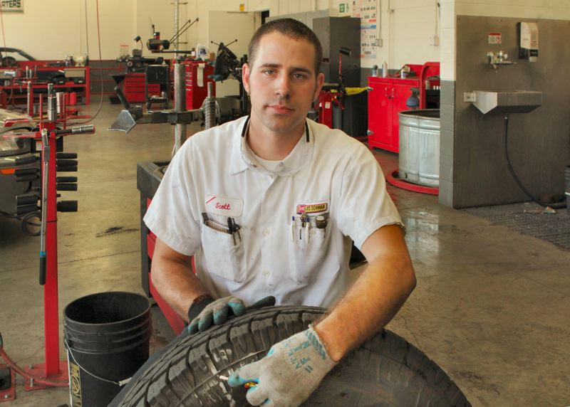 by: DAVID F. ASHTON - Les Schwab Tacoma Street Store Assistant Manager Scott Palmer shows where a vandals sturdy pin punctured and destroyed this almost-new tire.
