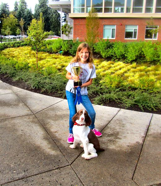 by: JANE A. KENNEY - The dog which won the most impressive ribbon, and then went on to take best of show, was an English Springer Spaniel named Joey - shown here in front of the new Reed Performing Arts Center building with his owner, Ellie B., and his awards. He was a rescue dog from a shelter, she said.