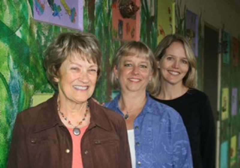 by: SUBMITTED PHOTO - From left, Lynne Detrick, Sarah Wright and Katie Topping stand by the art wall at Cedaroak Park Primary School, one of many art projects that MAP has provided support for.