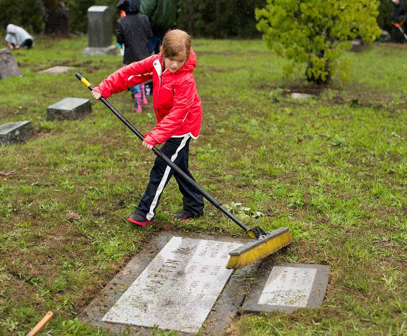by: NEWS-TIMES PHOTO: CHASE ALLGOOD - Myleanna Vernon, who helped come up with the cemetery-cleaning idea, sweeps off a grave marker. In addition to this project, the Scouts plan to visit a nursing home to share music, crafts, games and conversation with residents; and also to send Girl Scout cookies to troops in Afghanistan.