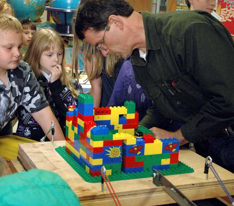 by:  ISABEL GAUTSCHI - Structural Engineer David Bugni hooks up a Lego building to an earthquake simulator (a wooden board on wheels shaken by a drill) as Dylan Nelms, from left, James Schalk and Samantha Warren gather round.