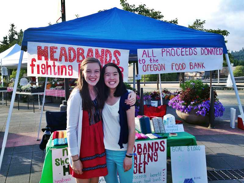 by: SUBMITTED PHOTO - Zoe Wong takes a break from vending at the Lake Oswego Farmers Market to spend time with a friend, Claire Murphy, left.