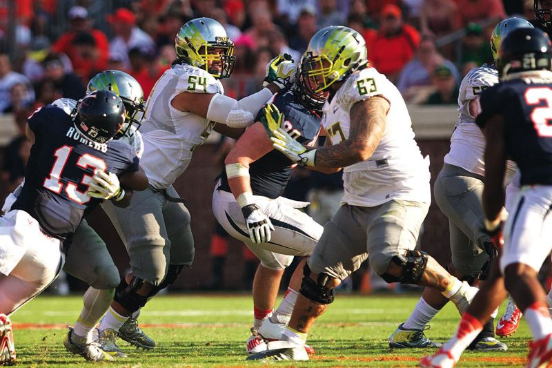 by: TRIBUNE PHOTO: JAIME VALDEZ - Oregon Ducks offensive linemen Hamani Stevens (second from left) and Mana Greig (right) block Virginia Cavaliers defenders in a 59-10 UO road win on Sept. 7. The front line duo has beat the odds to become starters and major players for Oregon.