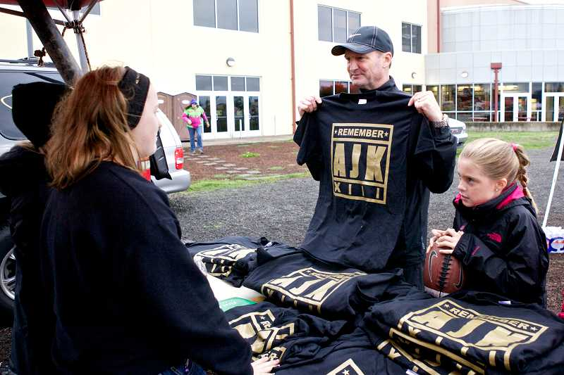by: TIMES PHOTO: JAIME VALDEZ - Marty Hawkins, who went to school with Jeff and Kim Keller, buys a T-shirt in honor of their son Andrew. Proceeds from the shirts will benefit the creation of a Community Plaza project at Southridge High School.