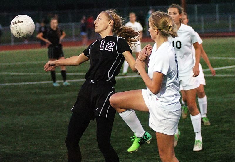 by: DAN BROOD - GOAL SCORERS -- Sherwood sophomore Allison Schwarm (left) and Tigard sophomore Natalie Bryant battle for the ball. They each scored a goal in last Thursday's match, which ended in a 1-1 tie.