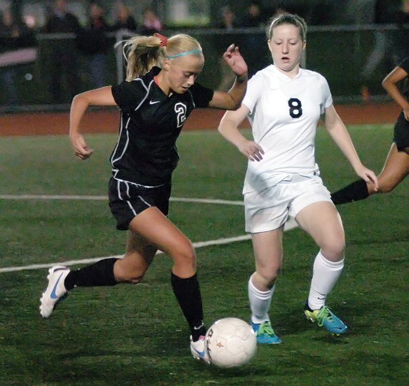 by: DAN BROOD - CLOSE MATCH -- Sherwood High School freshman Kaillen Fried (left) looks to get the ball up field against Tigard sophomore Ellie Freeman in last Thursday's contest.