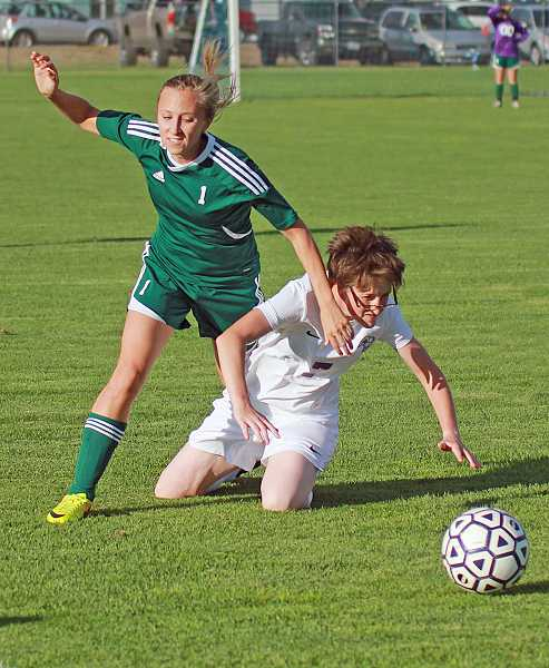 by: BILLY GATES/THE PIONEER - Madras defender Cassidy Brown tries to slide tackle the ball away from a North Marion midfielder in the Buffs' 1-1 tie with the Huskies on Thursday at Madras High School. If it wasn't for a penalty kick being stopped by the North Marion goalkeeper, Madras would have picked up their first win of the season. So far this season, the Buffs haven't won a match, but have earned ties in five of their seven matches.