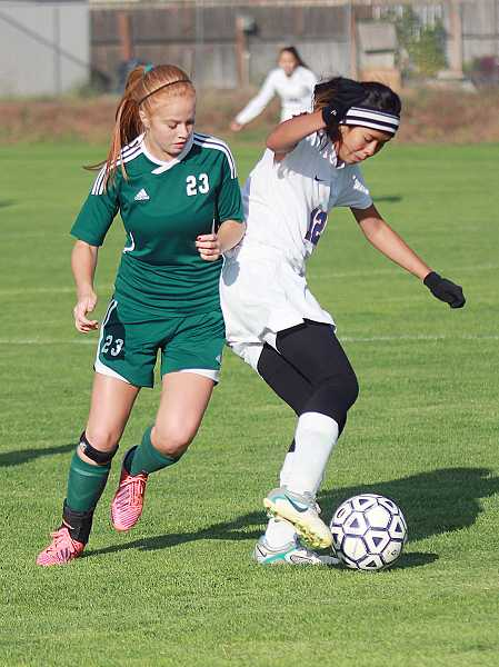 by: BILLY GATES/THE PIONEER - Madras' Itzel Romero (right) tries to work the ball around a North Marion defender.