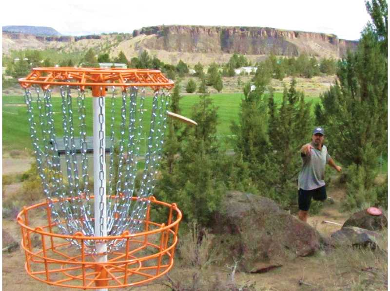 by: SUBMITTED PHOTO - Rancher Jim Tobish practices hitting Hole 6 of the disc golf course at CRR.