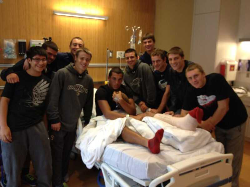 by: GRANT BOUSTEAD / COURTESY - Members of the Canby football team surround Sam Bodine, who had surgery Sept. 28 to repair broken bones in his left leg following an injury in the league-opening game against Oregon City. Bodine holds a game ball that was signed by teammates.