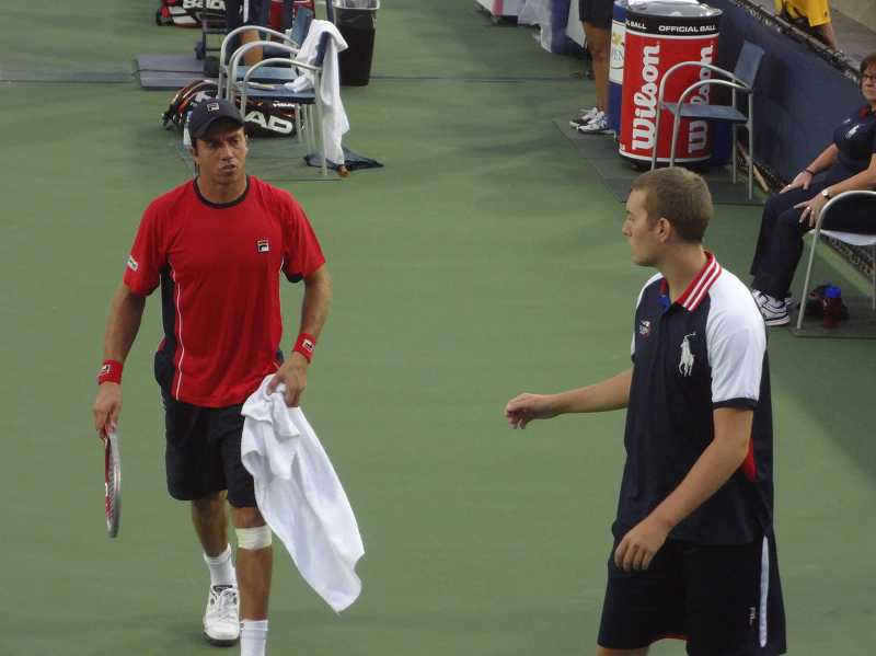 by: COURTESY PHOTO - North Marion alumnus Jeff Carroll (right) reaches for Carlos Berlocq's towel at the U.S. Open tennis tournament in New York. Carroll worked at the Grand Slam event for the second year in a row.