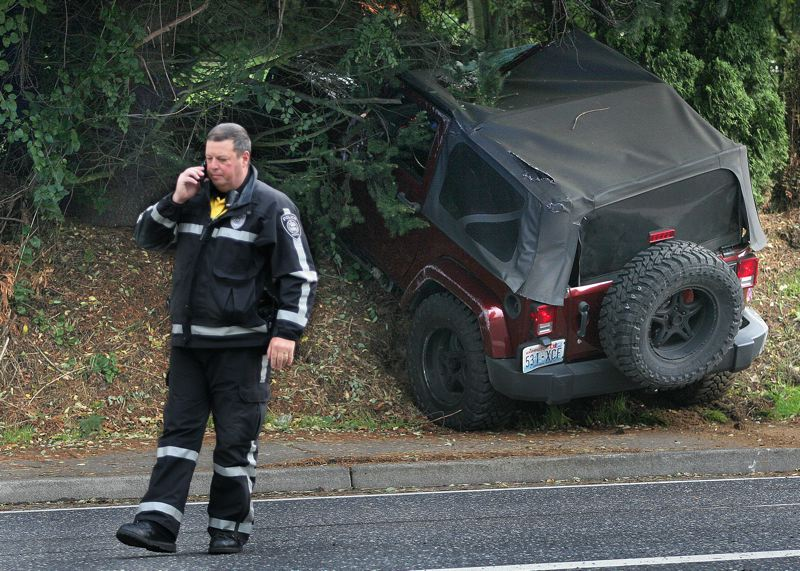 by: OUTLOOK PHOTO: JIM CLARK - A Gresham police officer stands in front of a stolen Jeep that crashed into three other vehicles, flipping over one of them before coming to a stop on the side of Northwest Eastman Parkway on Wednesday evening.