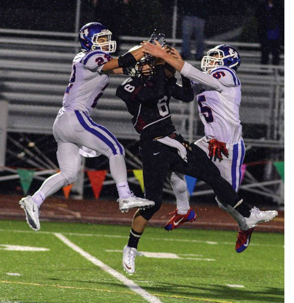 by: HILLSBORO TRIBUNE PHOTO: CHASE ALLGOOD - Glencoe senior Kyle Campbell makes a tough catch in between Hillsboro defenders Michael Gaskell (22) and Dylan Frederick (5) on Friday night.