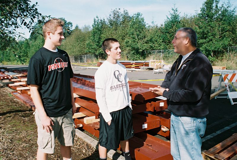 by: JOHN DENNY - Oregon City baseball players Jalen Satter (left) and Clay Valenzuela-Reece discuss the assembling of their new hitting facility with parent volunteer Martin Sprague. Sprague, who is project manager, said one of the first tasks for baseball players will be assembling thousands of nuts and bolts. When complete, Oregon Citys four-tunnel baseball hitting facility will be one of the biggest high school facilities of its kind in the state. Oregon City baseball coach Greg Lord is hopeful the community will rally around the baseball program with volunteer labor, so that the new hitting structure will be ready for use by the first of December.