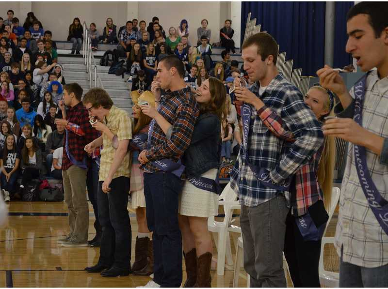 by: SUBMITTED PHOTO: JAKE YOUNG - The homecoming princesses feed pudding to the princes in a game during the Oct. 4 assembly.