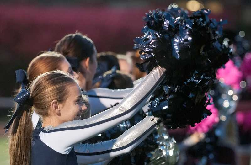 by: SPOKESMAN PHOTO: JOSH KULLA - Cheerleaders wave their pompoms during the national  anthem.