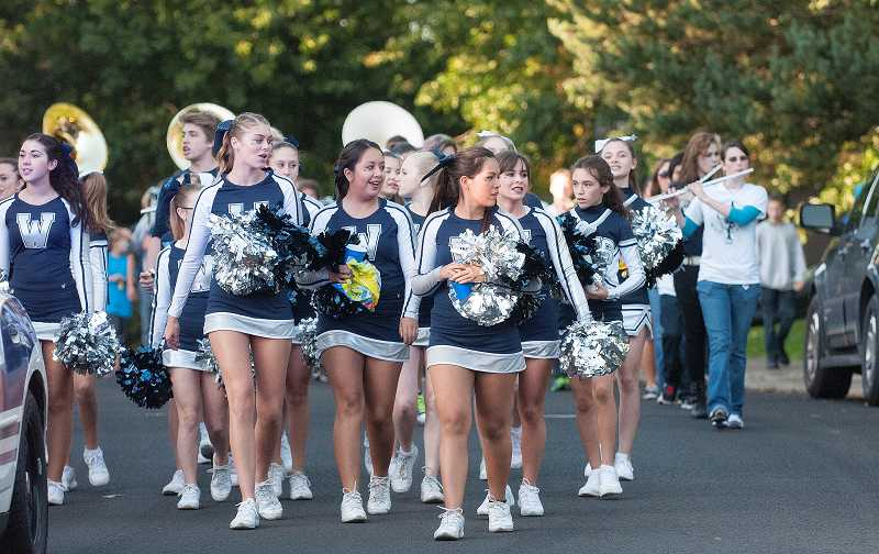 by: SPOKESMAN PHOTO: JOSH KULLA - Cheerleaders set the pace during the parade.
