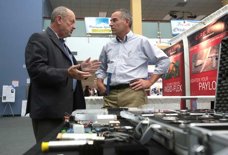 by: TIMES PHOTO: JONATHAN HOUSE - Beaverton Mayor Denny Doyle talks with Adapt Electronics President Gary Hilgeman during Tektronix's 13th annual OctoberBest Expo.