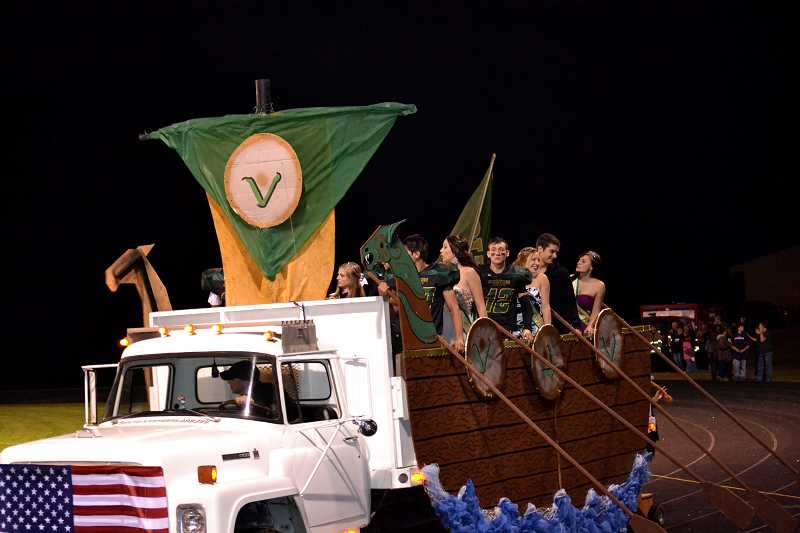 by: CINDY FAMA - Viking Ship brings Homecoming Court into Viking Stadium.