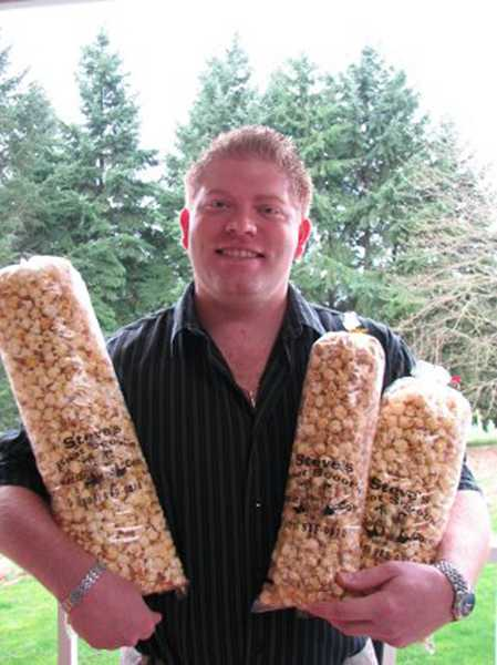 by: COURTESY PHOTO - Scott Baidenmann of Boot Scootin Kettle Corn hoists a few bags of his tasty treats.