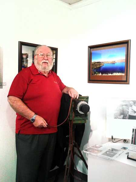 by: ISABEL GAUTSCHI - Photographer Boyd Holloway stands with an antique camera during the reception for his show at the Spiral Gallery on Friday, Oct. 4.