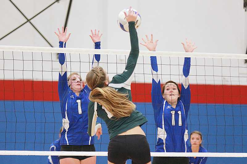 by: BILLY GATES/THE PIONEER - Madras' Elle Renault (left) and Keely Brown try to block an attack by an Estacada player during the Buffs' 3-1 win against the Rangers on Monday.