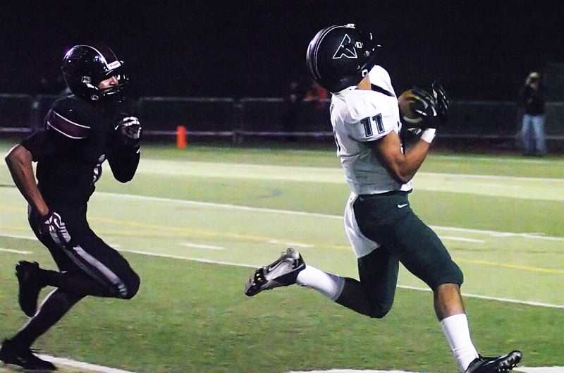 by: DAN BROOD - NICE CATCH -- Tigard High School senior receiver Daren Rodrigues (right) pulls in the football on his way to scoring on a 47-yard pass play in Friday's game at Tualatin.