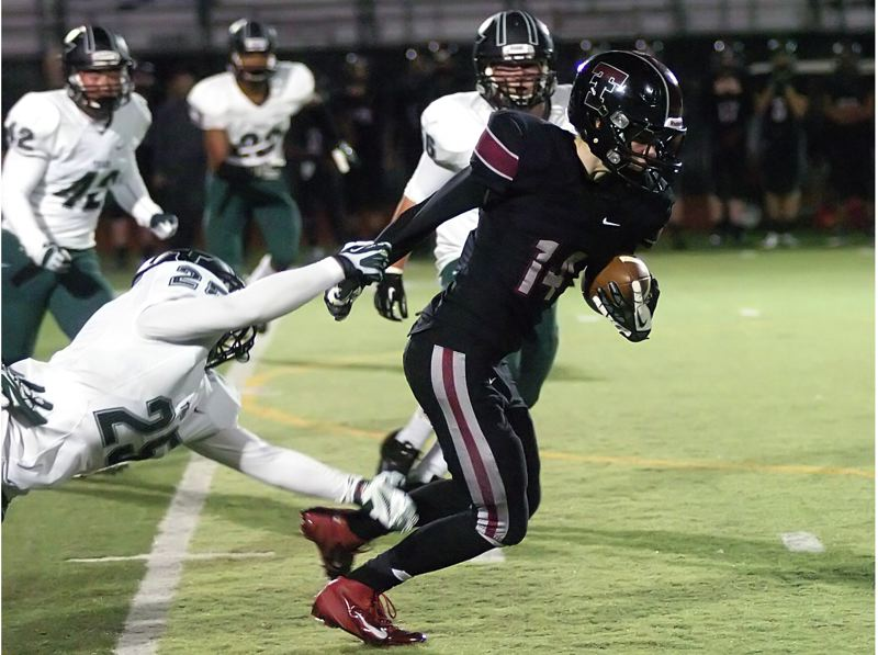 by: DAN BROOD - PLAYING HARD -- Tualatin senior receiver Robbie Ellis looks to pull away from Tigard senior Justin Alvarizares in Friday's game.