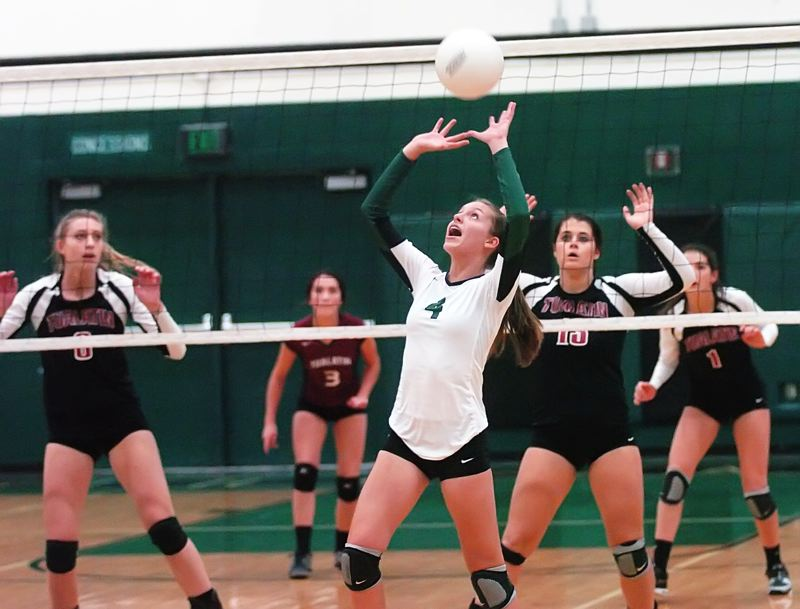 by: DAN BROOD - SETTING IT -- Tigard High School freshman Hannah Miller (4) sets the ball in front of a wall of Tualatin players, including, from left, Katie Savage, Beth Fanger, Haley Howarth and Sara Fanger. The Tigers won in three sets in the match held Tuesday at Tigard High School.